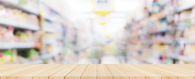 Tampo da mesa de madeira com o supermercado borrado no fundo, bandeira panorâmico.
