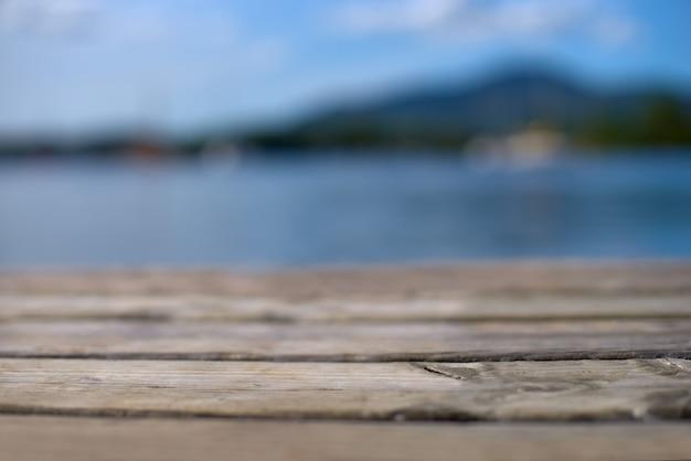 Tampo da mesa de madeira com praia tropical de cena turva da natureza e céu azul, conceito de plano de fundo de férias - pode ser usado para exibir ou montar seus produtos