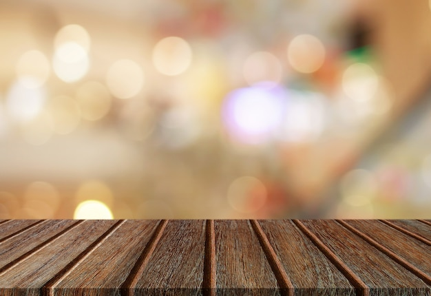 Tampo da mesa de madeira da prancha da perspectiva vazia com fundo abstrato da luz do bokeh para a montagem de seu produto.