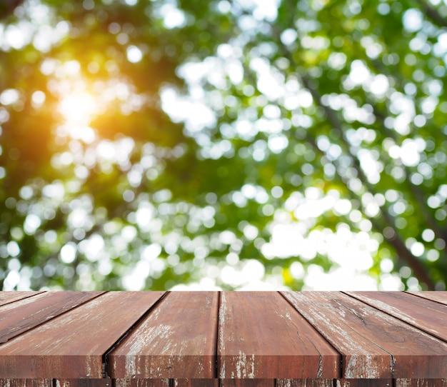Tampo da mesa de madeira da prancha do marrom vazio da perspectiva com fundo verde abstrato da natureza do bokeh. montagem do seu produto
