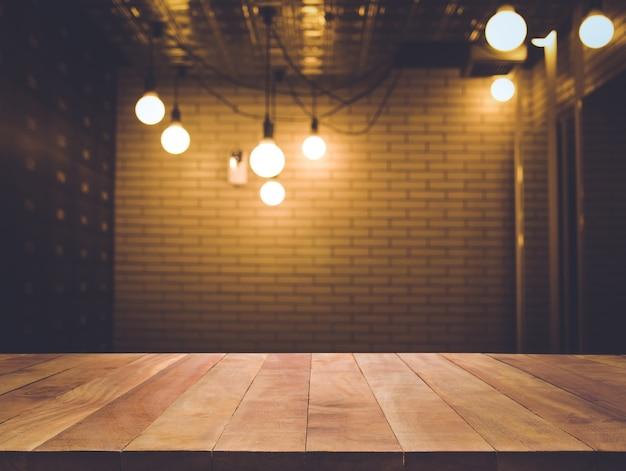 Tampo da mesa de madeira desfocado do balcão da loja de café com fundo de lâmpada