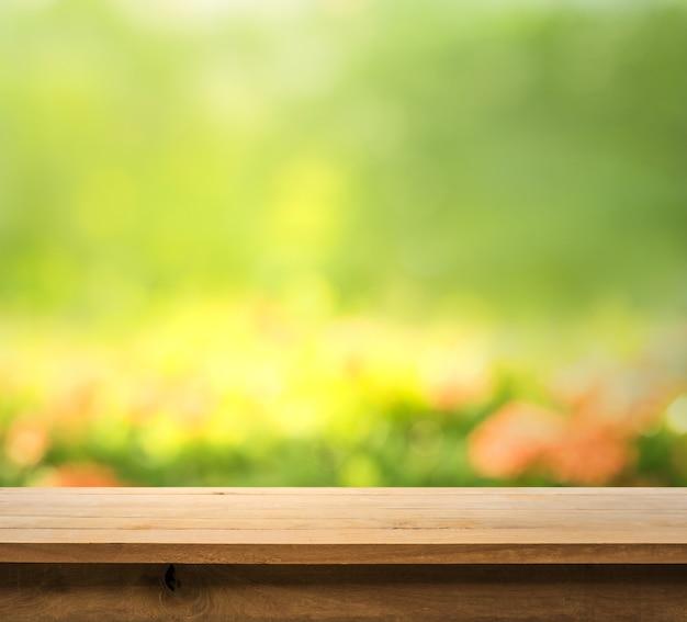 Tampo da mesa de madeira desfocado verde abstrato do jardim pela manhã
