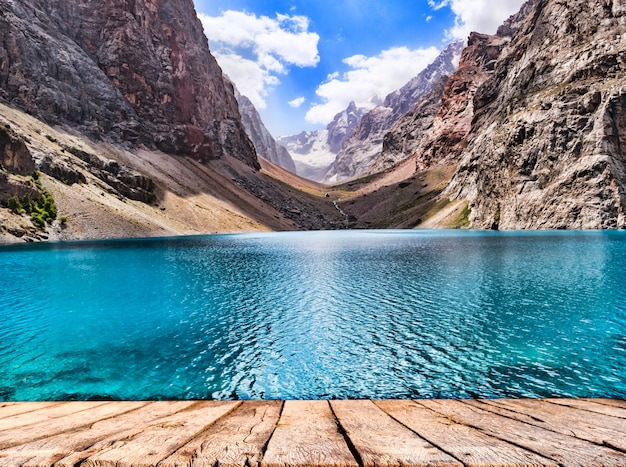 Tampo da mesa de madeira e lago de montanha com água azul-turquesa no sol na montanha rochosa