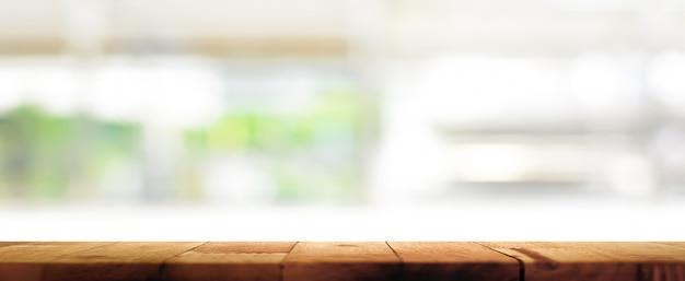 Tampo da mesa de madeira em desfocar o fundo da janela de cozinha