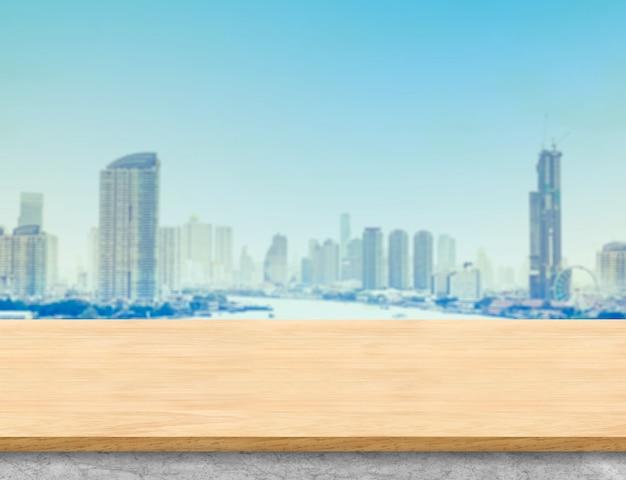 Tampo da mesa de madeira marrom e base de mármore branco com vista da paisagem do edifício da cidade