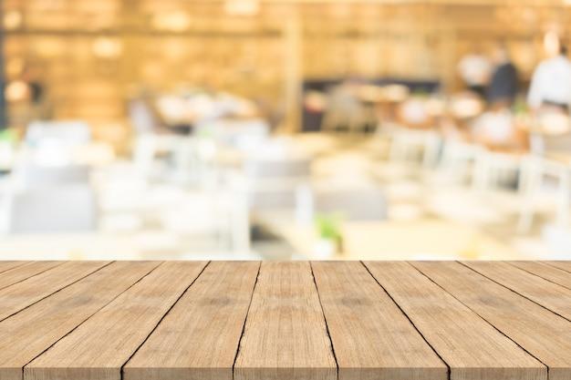 Tampo da mesa de madeira marrom vazio no fundo desfocado na cafeteria, copie o espaço para montagem do seu produto