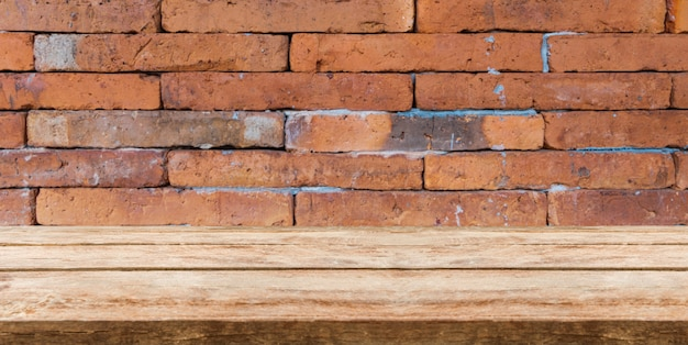 Tampo da mesa de madeira na frente do fundo do tijolo e espaço da cópia. produtos de exibição ou montagem