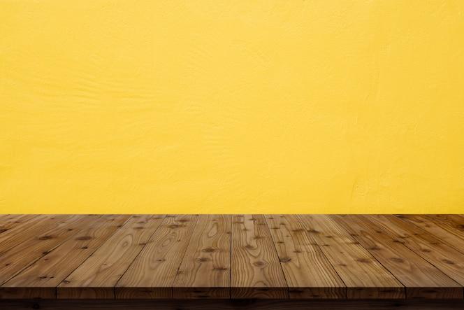 Tampo da mesa de madeira no fundo amarelo da parede.