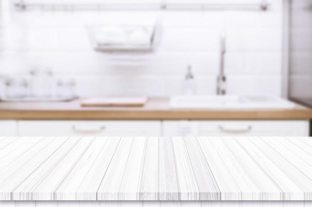 Tampo da mesa de madeira no fundo borrado da cozinha.