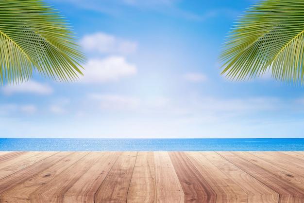Tampo da mesa de madeira no fundo borrado da praia para a exposição do produto.