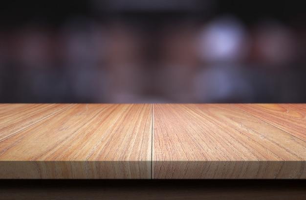 Tampo da mesa de madeira no fundo borrado escuro.