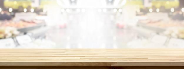 Tampo da mesa de madeira no fundo da bandeira de supermercado para exibir ou montagem de seus produtos