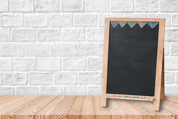 Tampo da mesa de madeira no fundo da parede de tijolo com quadro-negro vazio.