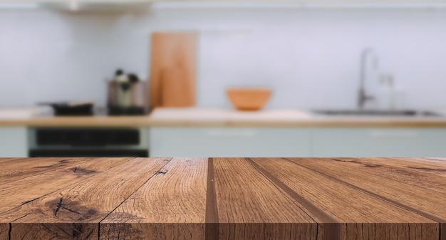 Tampo da mesa de madeira no fundo desfocado da cozinha