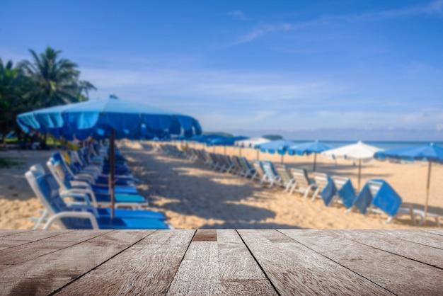 Tampo da mesa de madeira no guarda-chuva turva e pessoas relaxando na praia de areia branca