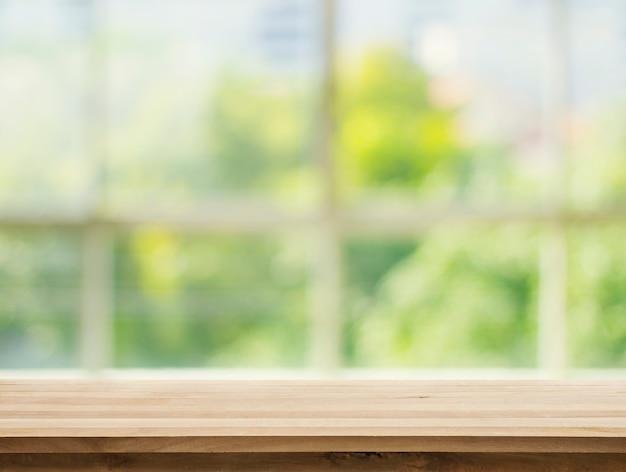 Tampo da mesa de madeira no jardim verde abstrato branco do fundo de vidro da janela