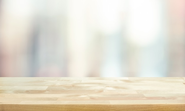 Tampo da mesa de madeira no vidro da janela desfocado, fundo da parede