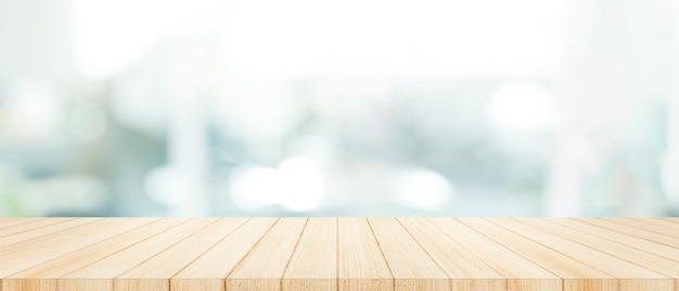 Tampo da mesa de madeira sobre com fundo da parede da janela de vidro do borrão.