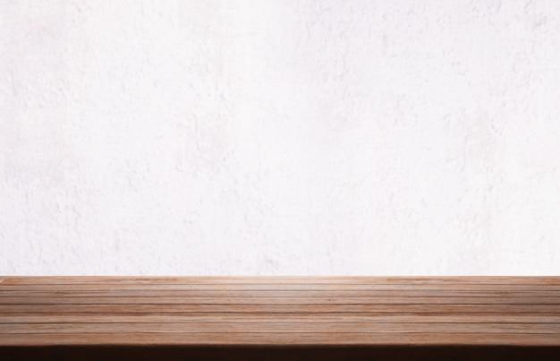 Tampo da mesa de madeira sobre o fundo branco do muro de cimento.