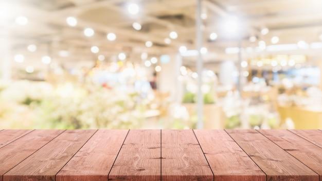 Tampo da mesa de madeira vazio borrado no fundo do shopping do bokeh.