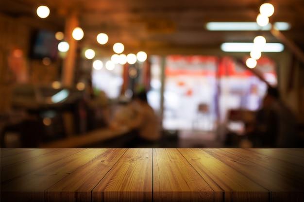 Tampo da mesa de madeira vazio com cafetaria borrada ou fundo do interior do restaurante.