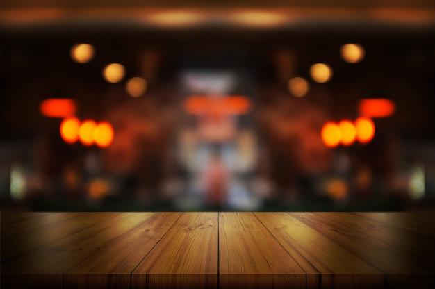 Tampo da mesa de madeira vazio com cafetaria borrada.