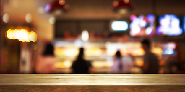 Tampo da mesa de madeira vazio com cafetaria do borrão ou fundo do interior do restaurante.