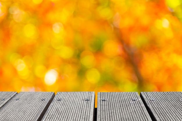 Tampo da mesa de madeira vazio com cor colorida do bokeh do jardim para criar.