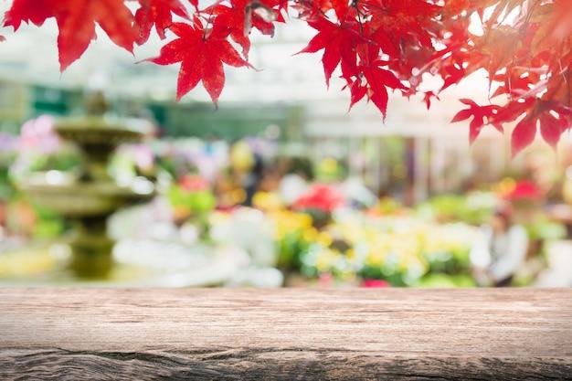 Tampo da mesa de madeira vazio e árvore de jardim borrada e fundo vermelho da folha de bordo.