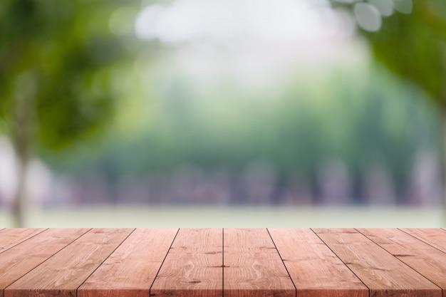 Tampo da mesa de madeira vazio e árvore e gramado verdes borrados no fundo do parque.