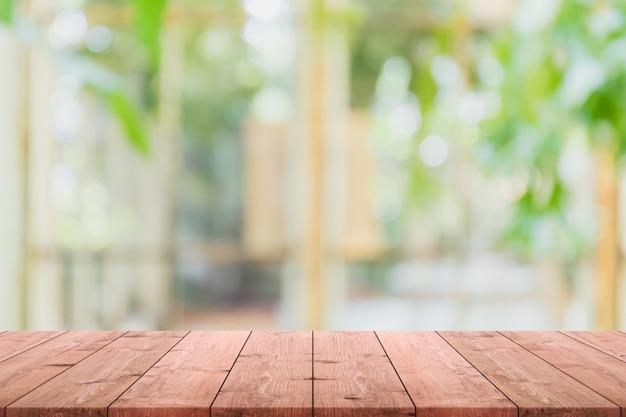 Tampo da mesa de madeira vazio e borrado da sala interior com opinião da janela do fundo verde do fundo do jardim da árvore.