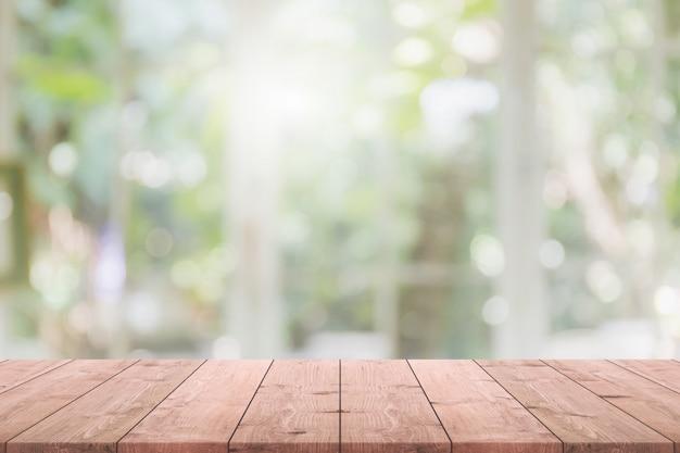 Tampo da mesa de madeira vazio e borrado do restaurante interior com vista da janela verde do fundo do jardim da árvore - pode ser usado para exibir ou montar seus produtos.