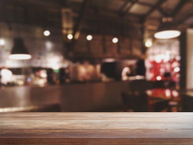 Tampo da mesa de madeira vazio e café borrado do bokeh e fundo do interior da cafetaria.