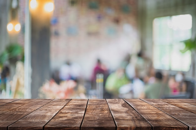 Tampo da mesa de madeira vazio e café borrado e fundo do restaurante.