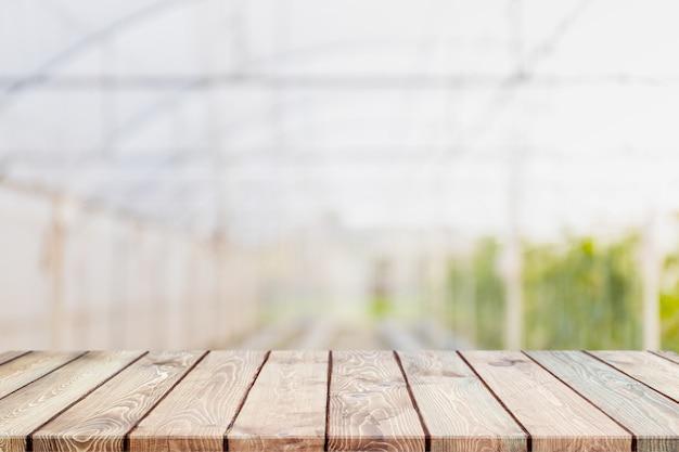 Tampo da mesa de madeira vazio e estufas borradas em explorações agrícolas.