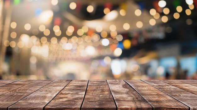 Tampo da mesa de madeira vazio e fundo interior desfocado do café e do restaurante - pode ser usado para exibir ou montar seus produtos.