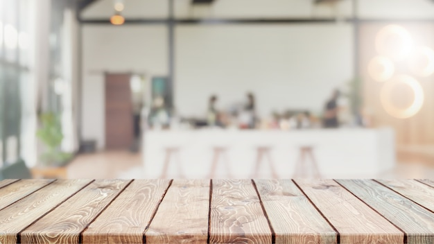 Tampo da mesa de madeira vazio e fundo interior turva de café, café e restaurante.