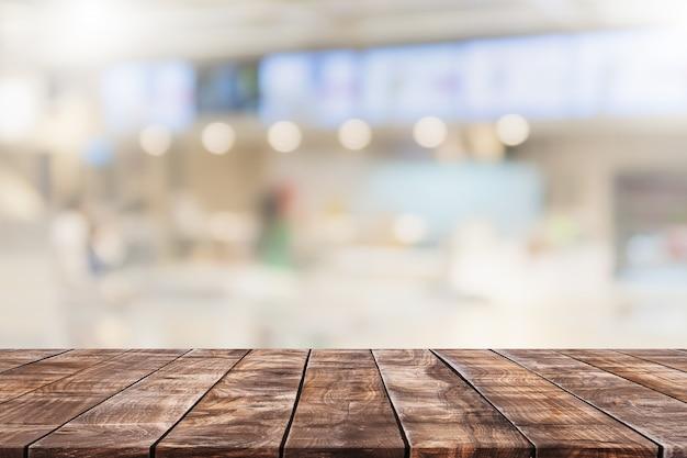 Tampo da mesa de madeira vazio e interior da janela de vidro desfocado