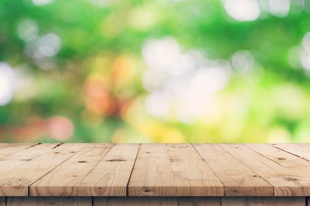 Tampo da mesa de madeira vazio e montagem verde da exposição do bokeh para o produto com espaço.
