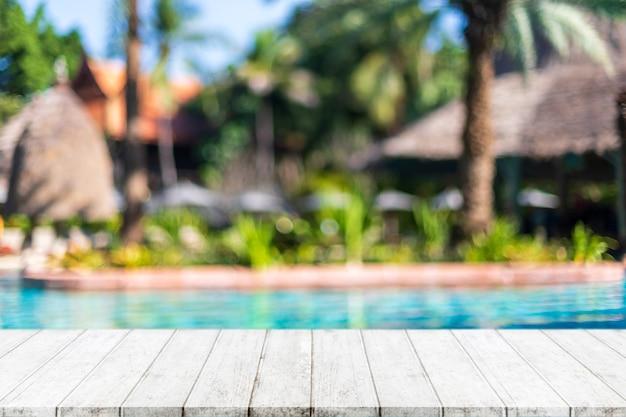 Tampo da mesa de madeira vazio e piscina turva em resort tropical no verão