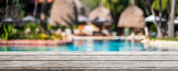 Tampo da mesa de madeira vazio e piscina turva em resort tropical
