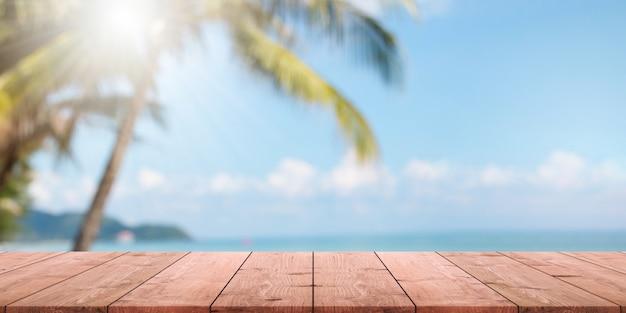 Tampo da mesa de madeira vazio e praia borrada do verão com fundo azul da bandeira do mar e do céu.