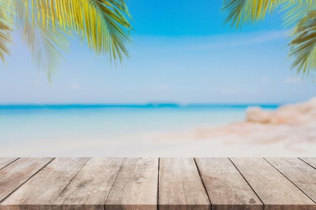 Tampo da mesa de madeira vazio e praia borrada do verão da palmeira com fundo azul do mar e do céu.