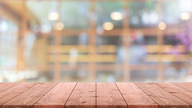Tampo da mesa de madeira vazio e restaurante e café com janela de vidro borrado