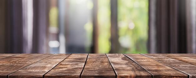 Tampo da mesa de madeira vazio e sala de estar desfocada no interior da casa com janela de cortina