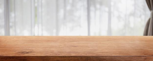 Tampo da mesa de madeira vazio e sala de estar desfocada