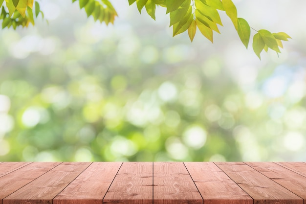 Tampo da mesa de madeira vazio e vista borrada do fundo verde do bokeh do jardim da árvore.