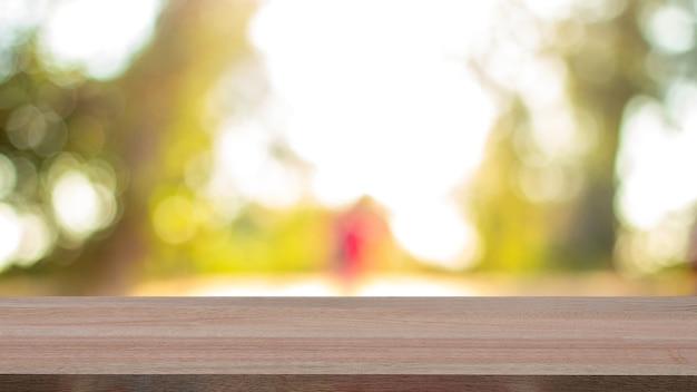 Tampo da mesa de madeira vazio em desfocar a natureza no fundo da manhã. para montagem do produto.