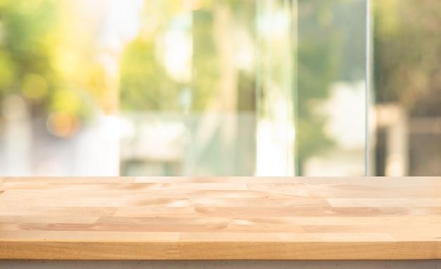Tampo da mesa de madeira vazio na visão borrada do vidro da janela abstrata. para exibição de produtos de montagem ou layout visual chave de design
