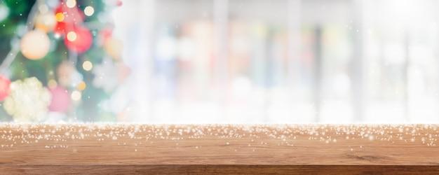 Tampo da mesa de madeira vazio no desfoque com bokeh árvore de natal e decoração de ano novo na janela